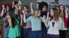 Carefree group of young friends dancing together at a house party Stock Footage