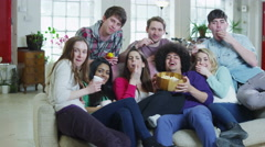 Happy group of friends relaxing on the sofa, eating popcorn and watching TV Stock Footage