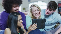Happy casual young friends laughing at what they see on a tablet computer Stock Footage