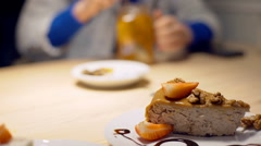View of delicious cake and girl mixing tea in the background, steadycam shot Stock Footage