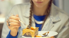 Girl sitting in the cafe and eating delicious cake with strawberries Stock Footage