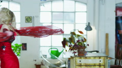 Young woman in a red dress spinning and dancing round her apartment Stock Footage