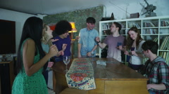 Happy and carefree group of young friends gathered around a piano at a party Stock Footage