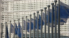 European Union flags wave Brussels EU Commission Berlaymont exterior sunny day Stock Footage