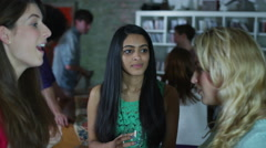 Three young girlfriends drinking and gossiping together at a house party Arkistovideo