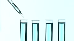 Liquid drop from laboratory glass pipette to test tube Stock Footage