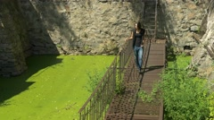 Young beautiful girl walks on thin ruined rusty metal bridge over green water. Stock Footage