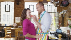 Happy young newlywed couple getting romantic in the kitchen Stock Footage