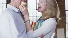 Happy mature couple getting romantic in the kitchen Stock Footage