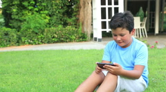 Young boy play smartphone on the grass  Stock Footage
