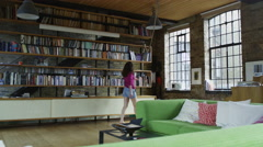 Attractive young woman relaxing in her stylish loft apartment Stock Footage