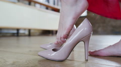 Glamorous woman in a red dress puts on her high heels Stock Footage