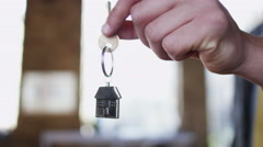 A key is held out with a shiny metallic key fob of a little house Stock Footage