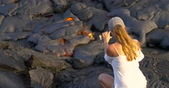 Girl taking picture flowing lava in Kilauea volcano Hawaii Stock Footage