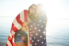 Two pretty girls wrapped in national American flag looking at camera on sunny da Stock Photos