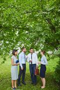 Team of co-workers talking under tree in park Stock Photos