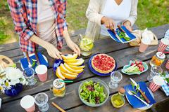 Human hands during preparation of food and serving table for picnic Stock Photos