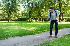 Modern game player with smartphone walking down road in park Stock Photos