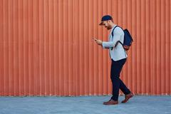 Contemporary active man playing popular mobile game in his smartphone outdoors Stock Photos
