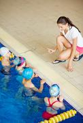 Young teacher explaining kids rules of swimming Stock Photos