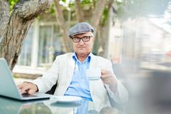 Elderly writer thinking of new ideas in cafe Kuvituskuvat