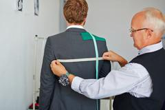 Modern tailor measuring back of male jacket Stock Photos