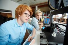 Handsome designer looking at new architectural model in 3d printer Kuvituskuvat