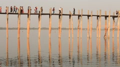 People and monks walking on U Bein Bridge.  Myanmar, Burma Stock Footage