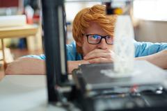 Engineer looking at architectural model in 3d printer in working environment Stock Photos