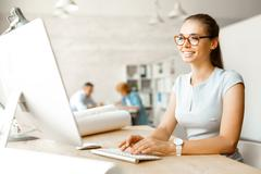Young designer sitting in front of computer monitor in office Stock Photos