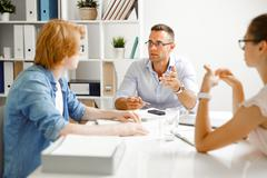 Group of young creative designers having conversation in office Stock Photos