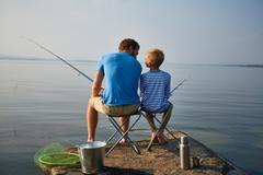 Boy and his father with rods sitting on chairs by lake Stock Photos