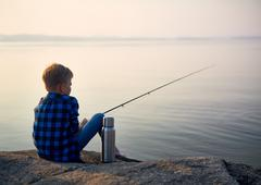 Little boy with rod waiting for fish by river Stock Photos
