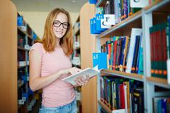 Cute girl with open book reading in college library Stock Photos