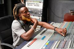 Handsome sound operator working in audio studio Stock Photos