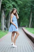 Spring beautiful woman in summer dress walking in green park enjoying weekend Stock Photos