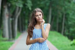 Spring beautiful woman in summer dress walking in green park enjoying weekend Stock Photos