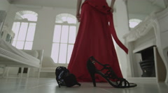 High heeled shoes and a crumpled evening gown on the floor Stock Footage