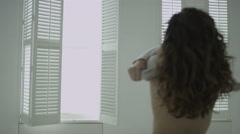 Beautiful woman bathed in morning sunlight as she pulls on her clothes Stock Footage