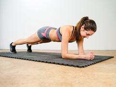 Young woman doing elbow plank Stock Photos