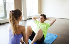 Woman with personal trainer doing sit ups in gym Stock Photos