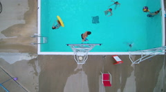 Aerial pull away of children playing in pool at summer camp Stock Footage