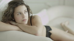 Beautiful model in lingerie reclines on a chaise and relaxes in her boudoir Stock Footage