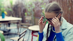 Pretty girl taking off glasses in the outdoor cafe and having a headache Stock Footage