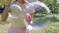 Girl in a yellow T-shirt and pink skirt blowing bubbles in the park Stock Footage