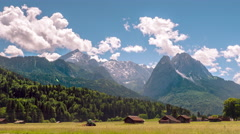 Beautiful countryside dramatic mountain peaks blue sky clouds Alps Zugspitze Stock Footage