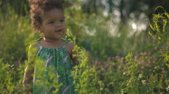 Handsome African-American child in the green grass on the nature Stock Footage