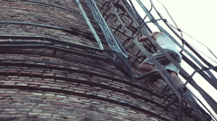 Extreme sports. Young men descend the metal stairs of a brick factory chimney Stock Footage