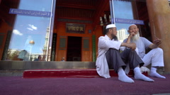 Elderly Muslims rest  and chat outside Mosque after making Jumah pray Stock Footage