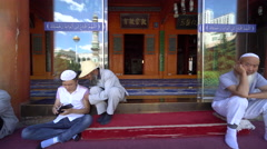 Elderly Muslims rest  and chat outside Mosque after making Jumah prayer Stock Footage